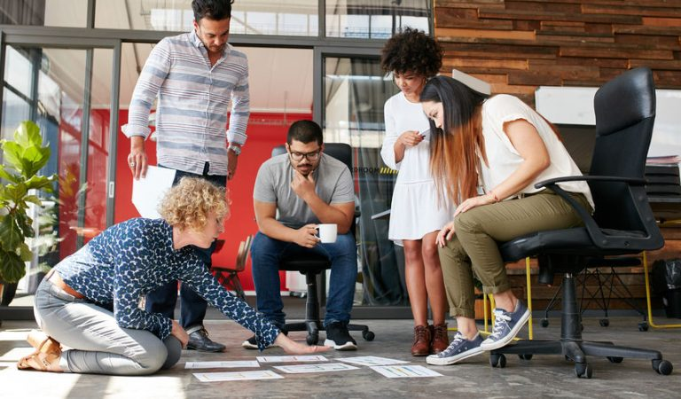 52328689 - creative people looking at project plan laid out on floor. mixed race business associates discussing new project plan in modern office.